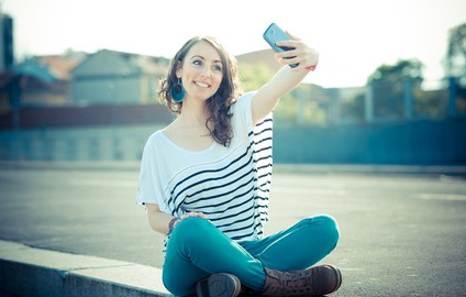young beautiful brunette woman selfie with smart phone
